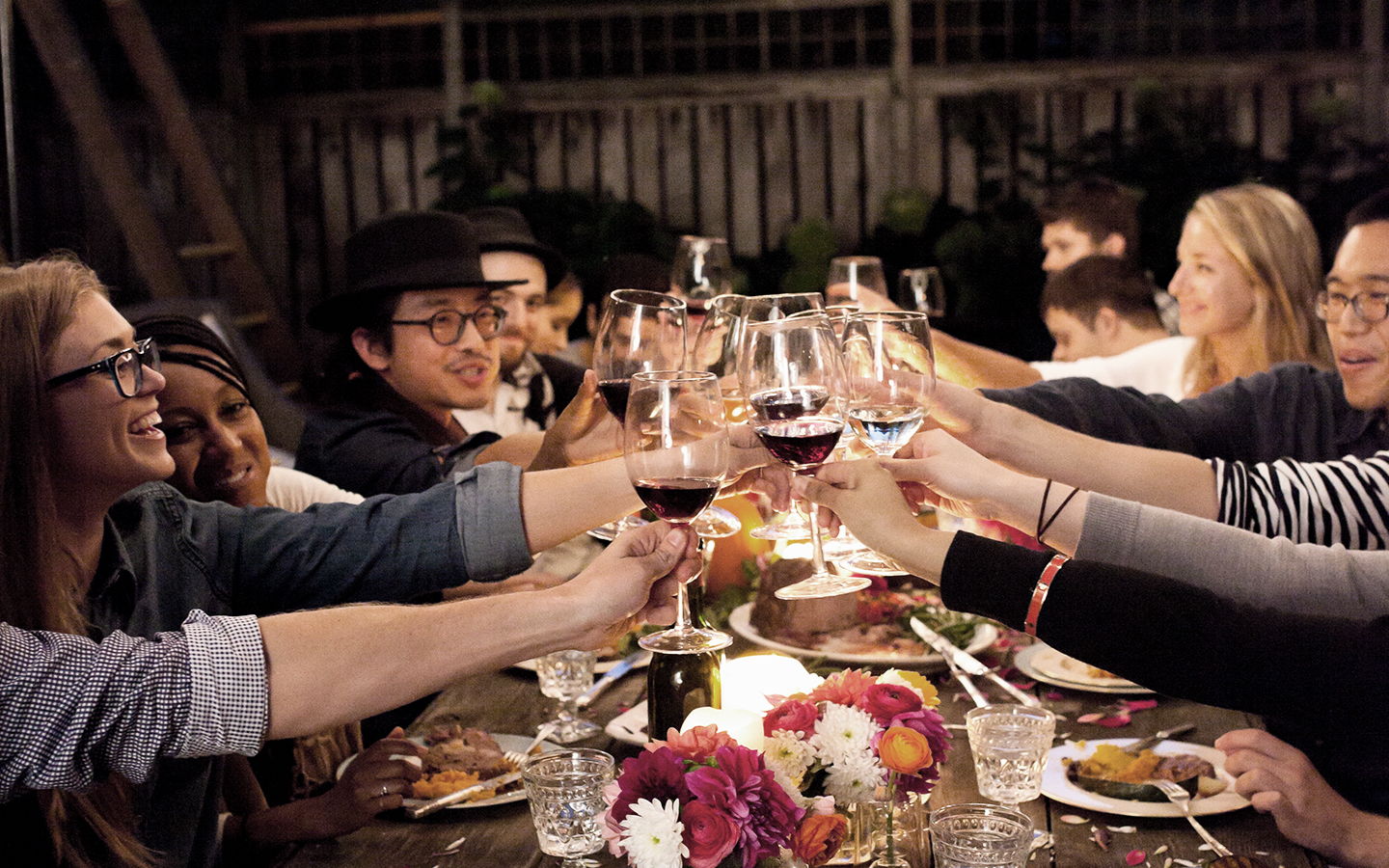 Friends enjoying dinner outside, raising their glass for a toast.
